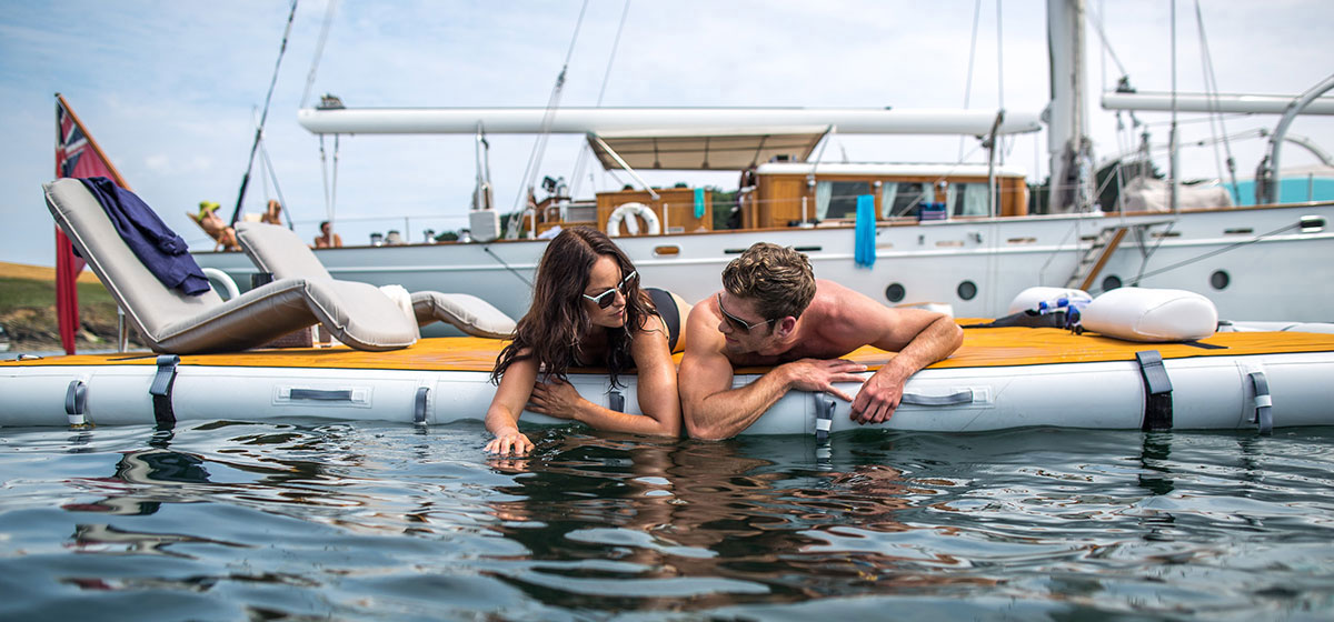 Couple lying at waters edge on inflatable platform - Nautibuoy Marine