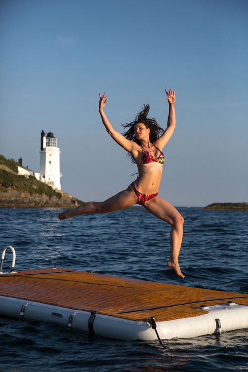 Woman dancing on inflatable platform on the sea - Nautibuoy Marine