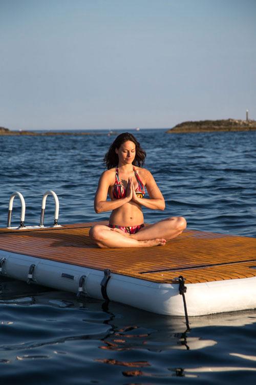 Woman meditating on inflatable platform on the sea - Nautibuoy Marine