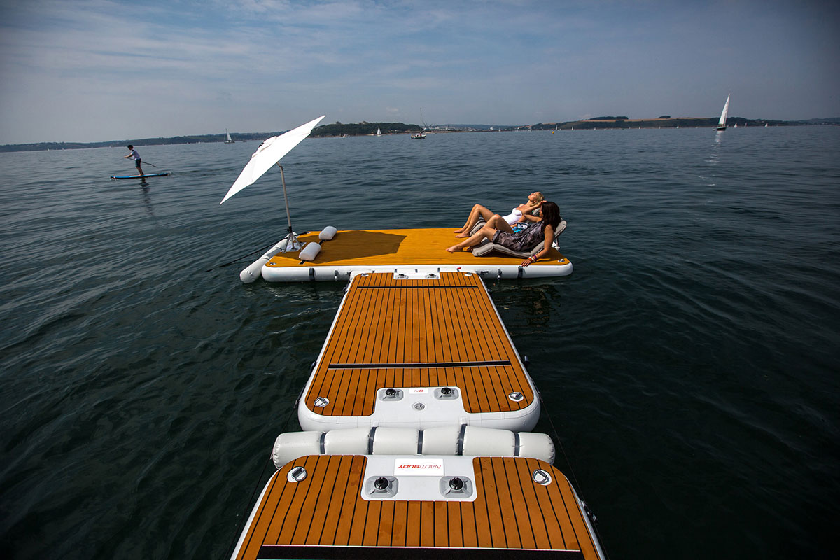 2 women sunbathing on t-shape inflatable jet ski dock with sun umbrella - Nautibuoy Marine