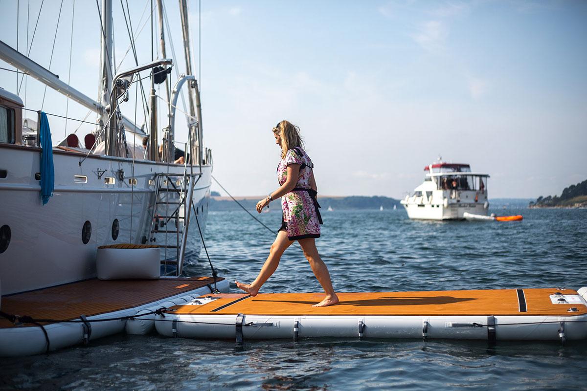 Woman walking down stable inflatable platform - Nautibuoy Marine