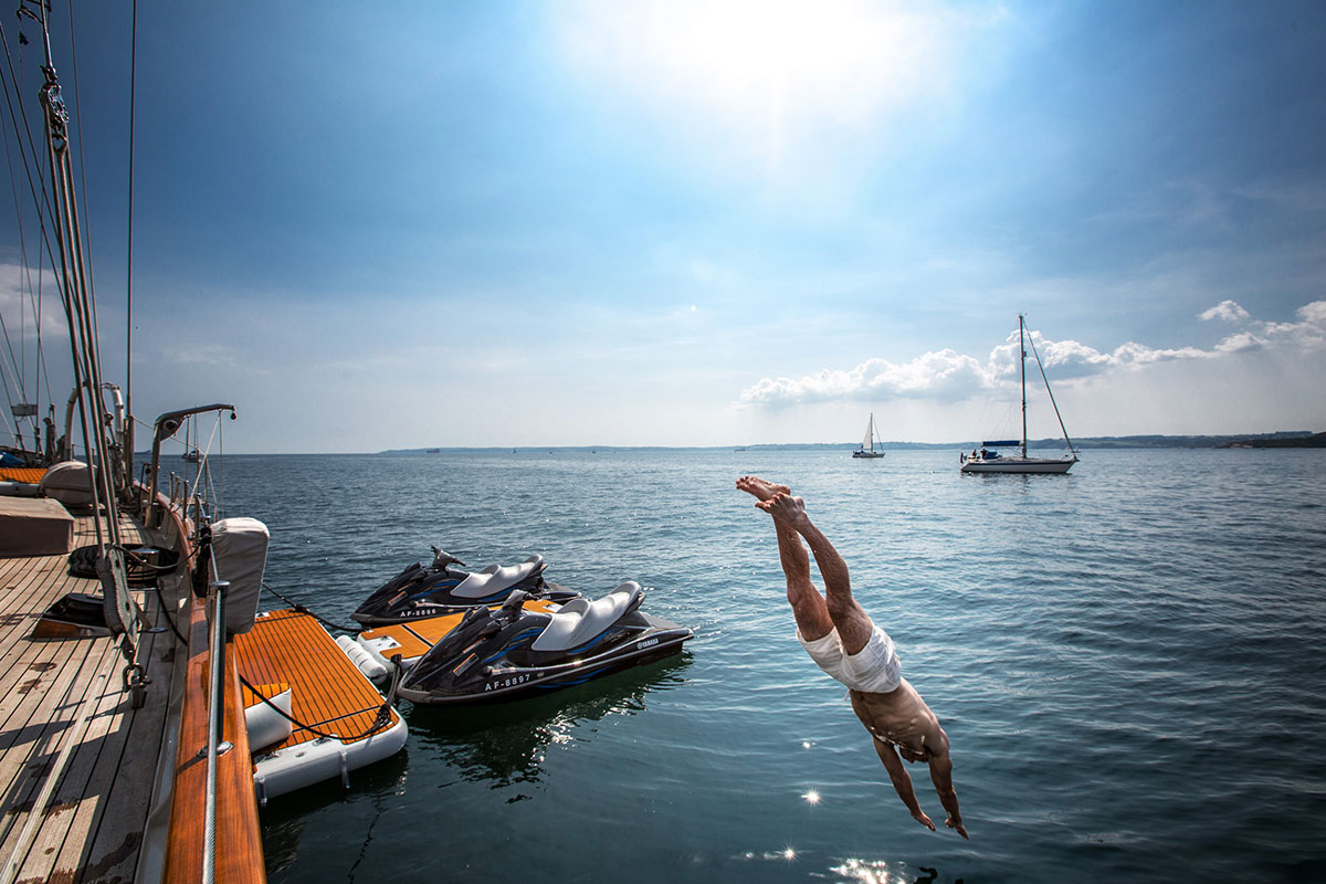 Man diving from yacht with jet ski dock in the background - Nautibuoy Marine