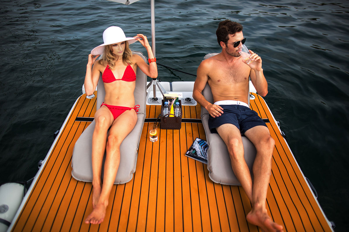People relaxing on reclining chairs on inflatable platforms with sun shade - Nautibuoy Marine