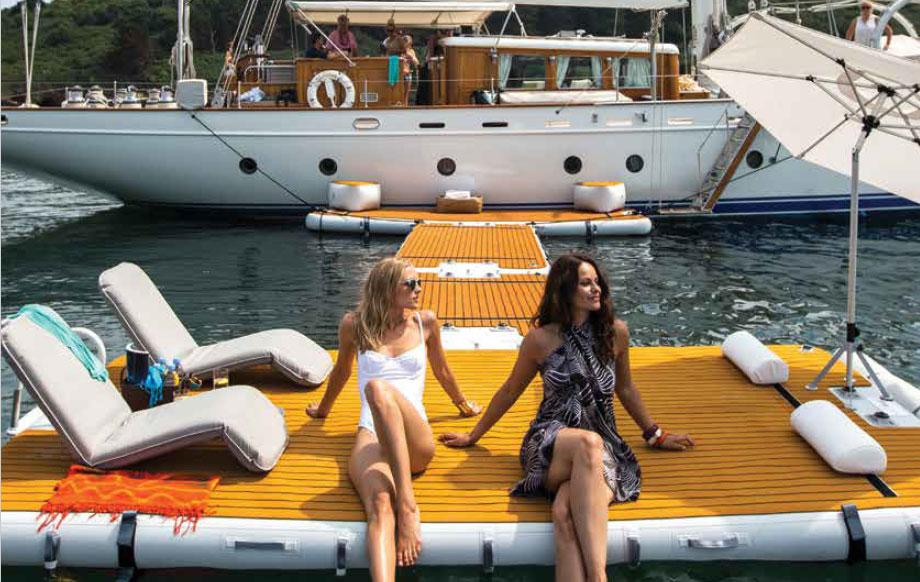 2 women sitting on waters edge on an inflatable jet ski dock - Nautibuoy Marine