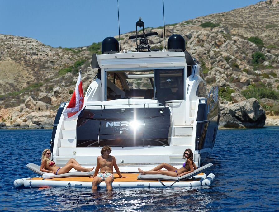 People relaxing on inflatable platform on the back of a motorboat - Nautibuoy Marine