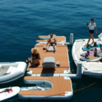 Woman serving drinks on inflatable platform at the back of a yacht - Nautibuoy Marine