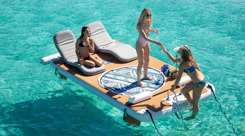 3 women enjoying inflatable private island swimming platform with ladder - Nautibuoy Marine