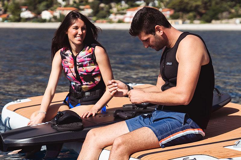 Man and Woman sitting on edge of inflatable platform with efoil board - Nautibuoy Marine